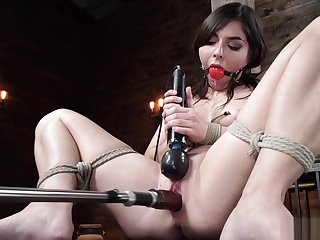 Brunette in suspension machine fucked