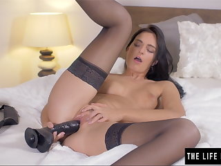 Shaved beauty pushes a fat black dildo dominant